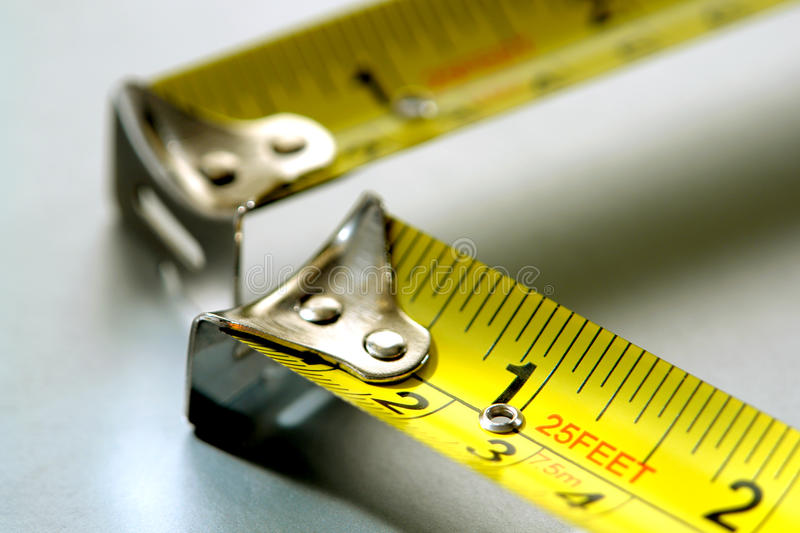 Measure Twice Cut Once with Two Tape Measures stock photo