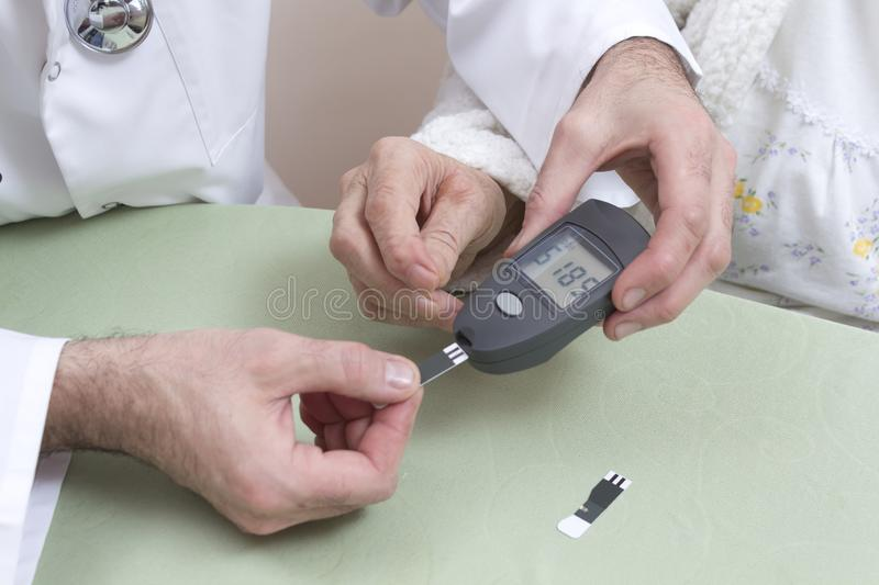 Measurement of the glucose meter with an old woman. The doctor`s hands hold a black glucometer. stock photography