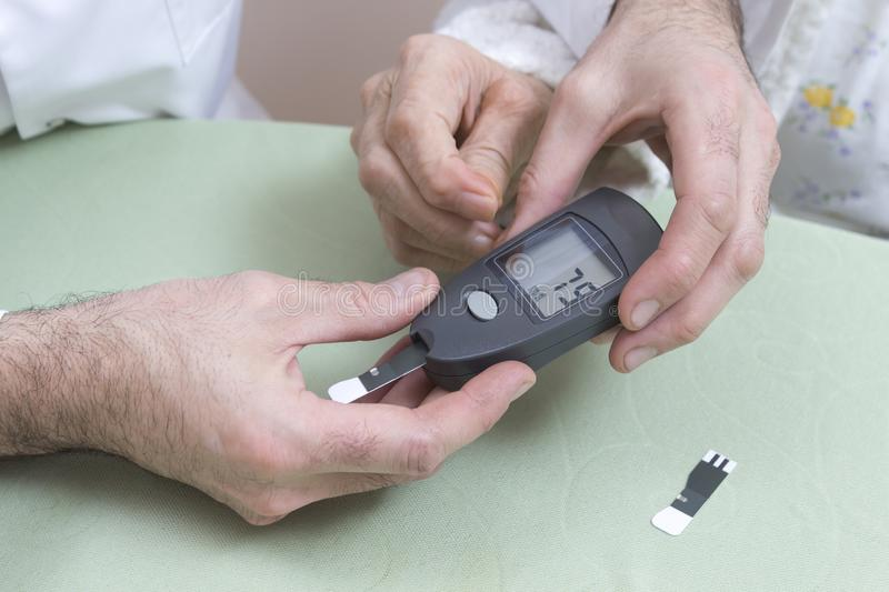 Measurement of the glucose meter with an old woman. The doctor`s hands hold a black glucometer. stock images