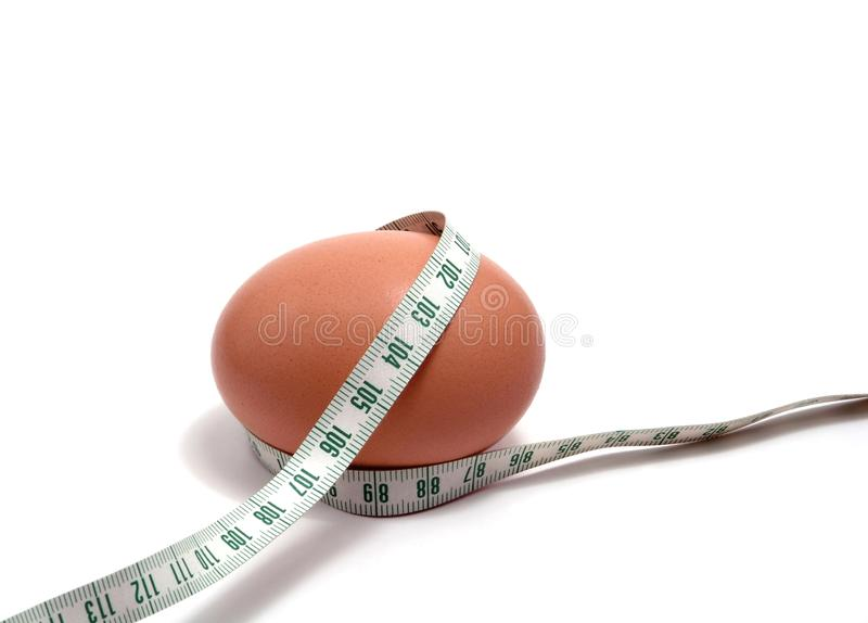 Measurement tape wrapped around the egg stock photos