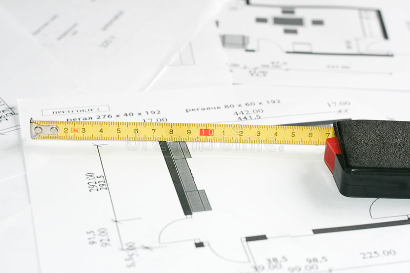 Measurement tool over blueprints royalty free stock images