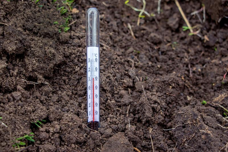 Measurement using a soil temperature thermometer in the spring to determine the readiness of the soil to plant crops_ royalty free stock images