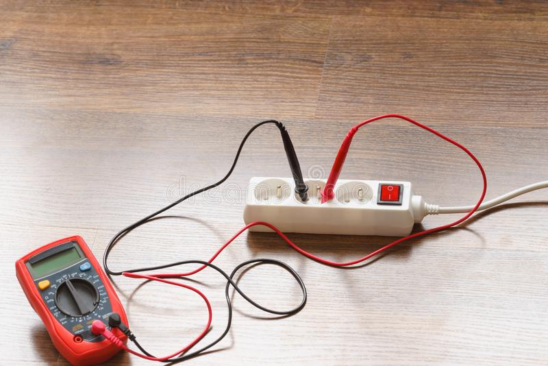 Measurement voltage in electrical socket with multimeter royalty free stock photography