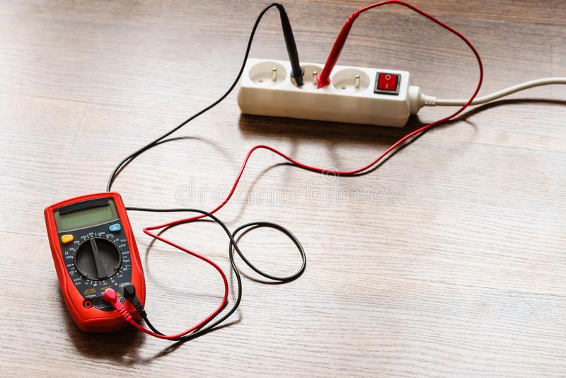 Measurement voltage in electrical socket with multimeter royalty free stock image
