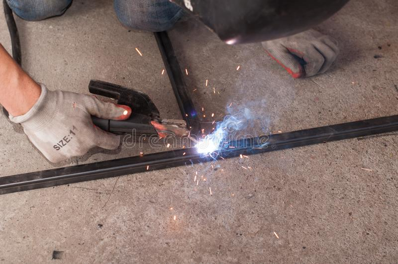 Measurement and welding tool. The worker welds a metal structure stock images