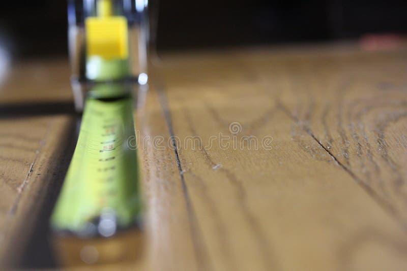 Measurer di misura di nastro sul pavimento di legno immagini stock