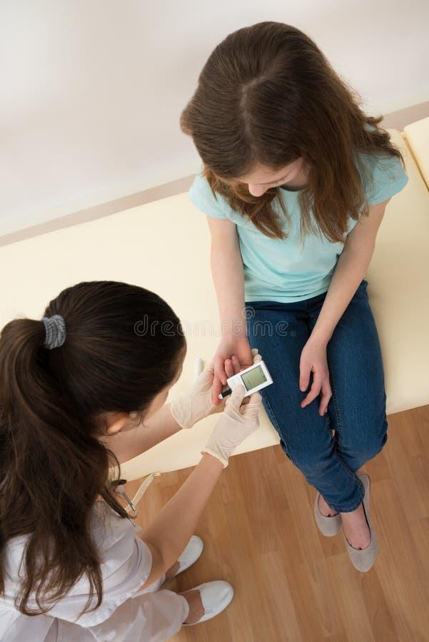Measuring医生女孩的血糖水平 免版税库存照片