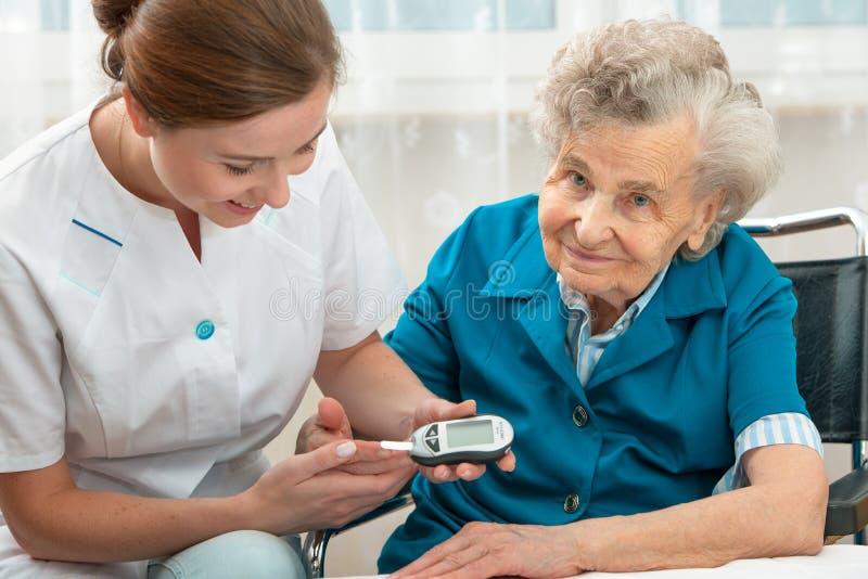 Measuring blood glucose level. Female nurse measuring blood glucose level of senior woman royalty free stock images