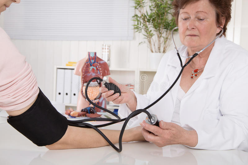 Measuring blood pressure with device instrument at doctor. Two w. Measuring blood pressure for prevention with device instrument at doctor. Two woman stock photos