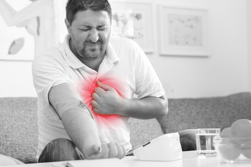 Measuring blood pressure. Man measuring blood pressure. Black and white. Chest pain highlighted in red stock image