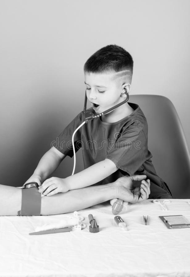 Measuring blood pressure. Medical examination. Medical education. Boy cute child future doctor career. Health care. Kid. Little doctor sit table with royalty free stock photos