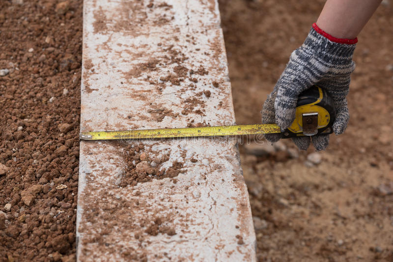 Measuring concrete at construction site with tape measure royalty free stock photo