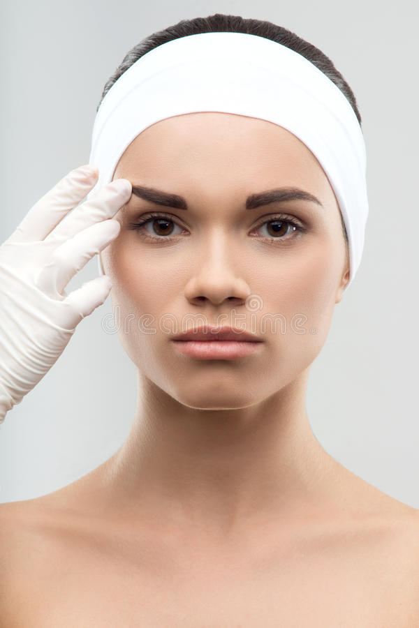 Measuring the correct proportion of eyebrows. Closeup portrait of young attractive woman being measured the correct proportion of eyebrows by surgeon in gloves royalty free stock image