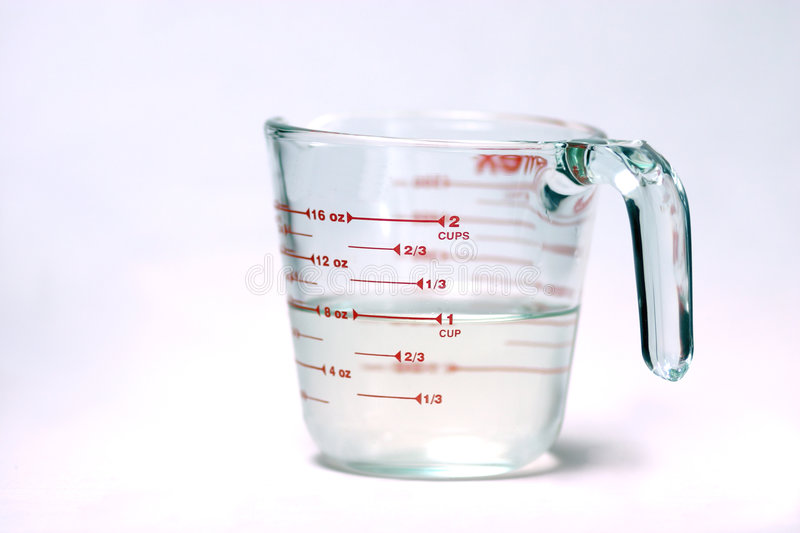 Measuring cup. With shallow DOF to blur out the measurements on the opposite side. Focus is on the US measurements. Also is half full...or half empty...however royalty free stock image