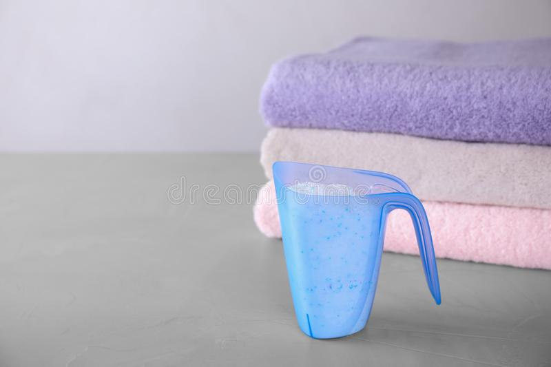 Measuring cup of laundry powder and clean towels on grey table against light background. Space for text royalty free stock photo