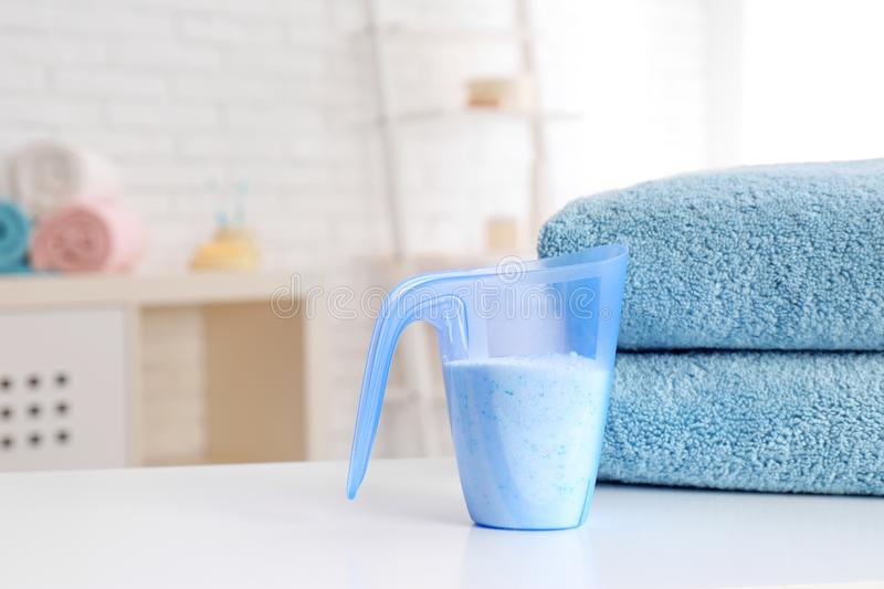 Measuring cup with washing powder and clean towels. On table indoors, space for text. Laundry day stock photos