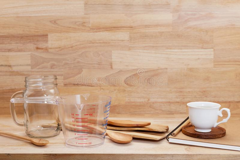 Measuring cup and wooden spoon, cooking supplies on wood background.  stock image