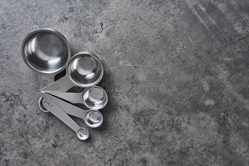 Measuring cups on black concrete background. stock image