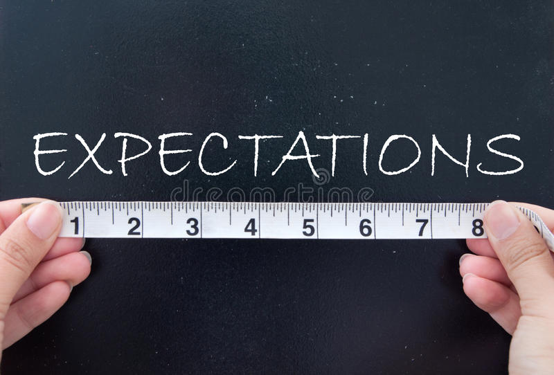Measuring expectations. Tape measuring expectations on a chalk board royalty free stock image