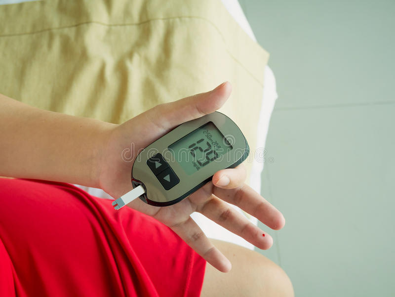 Measuring glucose level with digital glucose meter. Asian woman measuring glucose level with digital glucose meter, diabetes test royalty free stock photo