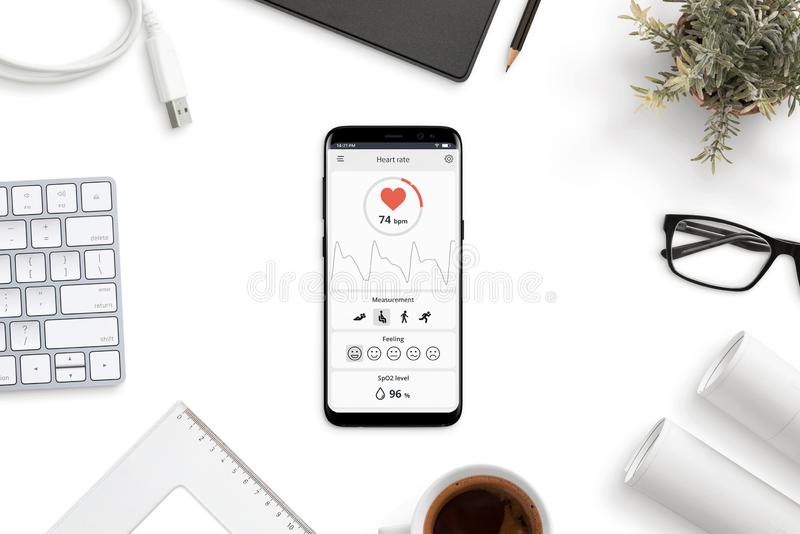 Measuring heart rate, beats per minute app on modern smart phone on office desk royalty free stock photos