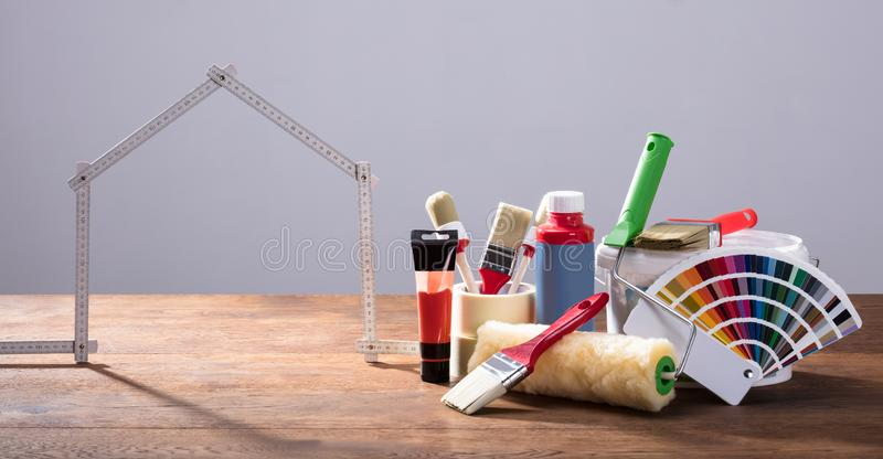 Measuring House Tape With Different Painting Equipments. On The Wooden Table Against The Gray Background stock photos