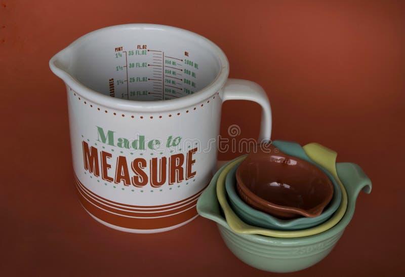 Measuring jugs. Ceramic colored measuring jugs stock photos