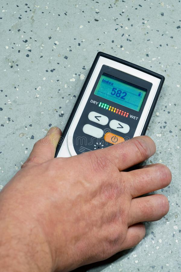 Measuring moisture. Man measuring moisture of the floor with moisture meter. Vertical image with space for text stock photo