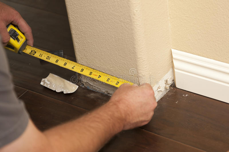 Measuring for New Baseboard with Bull Nose Corners and New Laminate Flooring. Contractor Measuring for New Baseboard with Bull Nose Corners and New Laminate stock photo
