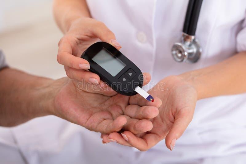 Measuring Patient医生的血糖水平 免版税库存图片