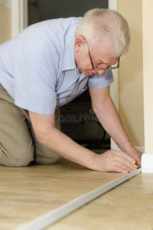 Measuring for Repairs. A senior adult man measuring new quarter round to replace the old on his baseboards royalty free stock photos