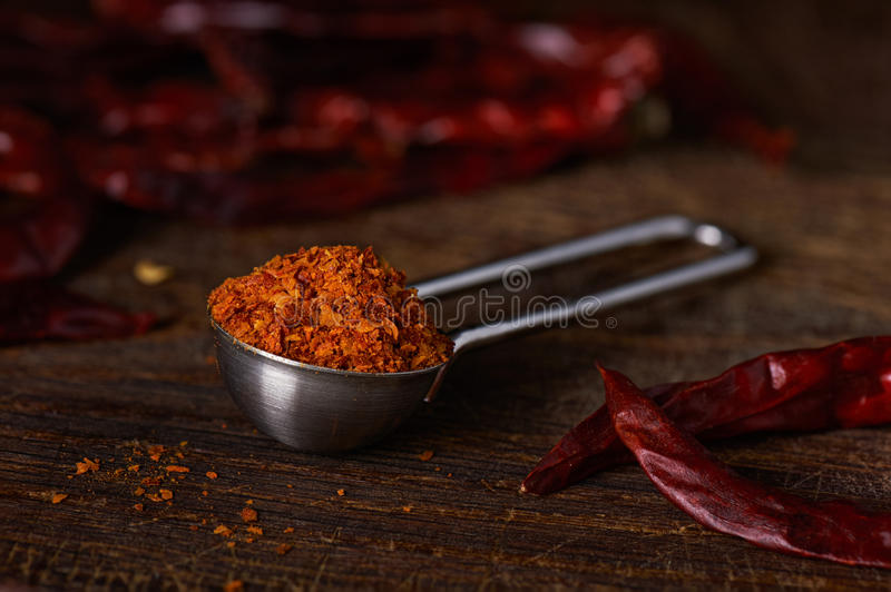 Measuring spoon with ground pepper. On a wooden surface stock images