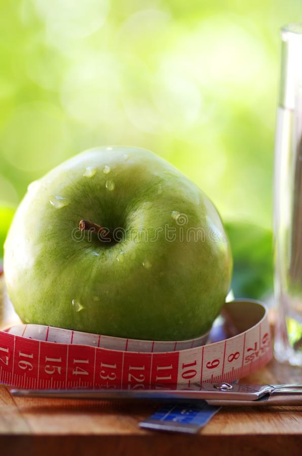 Measuring tape,apple and scissors stock images