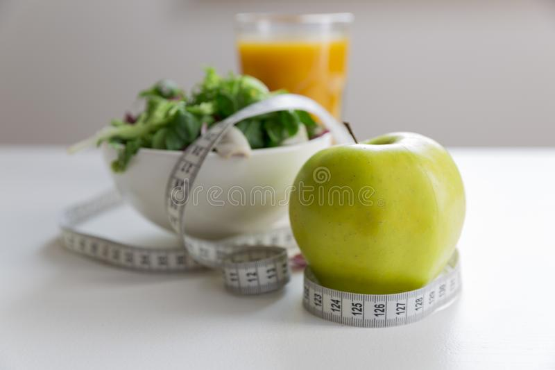 Measuring tape around the apple, bowl of green salad and glass of juice. Weight loss and right nutrition concept.  stock photo