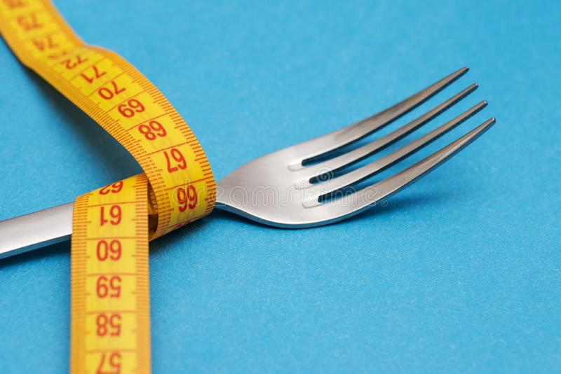 Measuring tape with fork on blue background. Concept of weight loss. Weight management. Healthy lifestyle. Weight loss health. Issue. Diet concept stock image