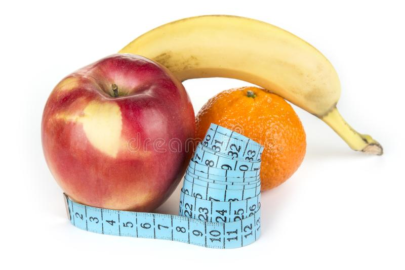 Measuring tape and a fruit. Diet and weight loss concept.  royalty free stock images