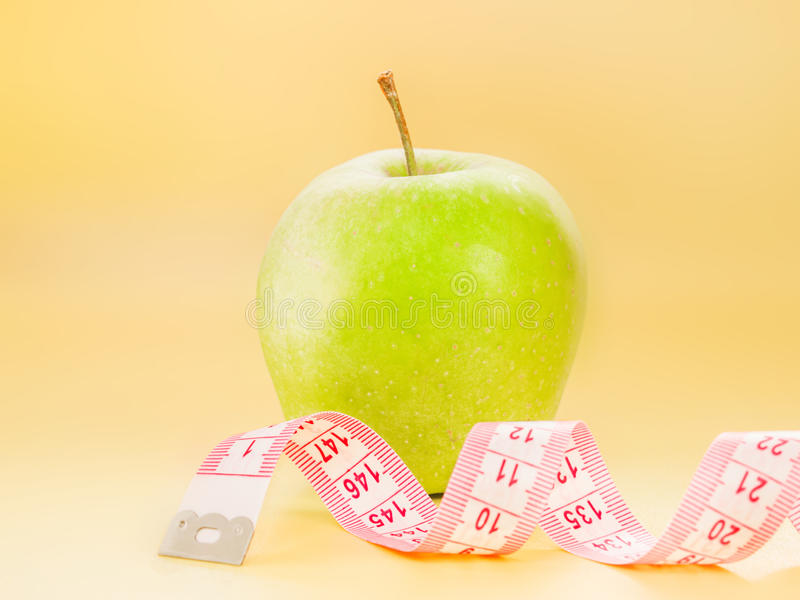 Measuring Tape And Green Apple As A Symbol Of Diet Stock Photo