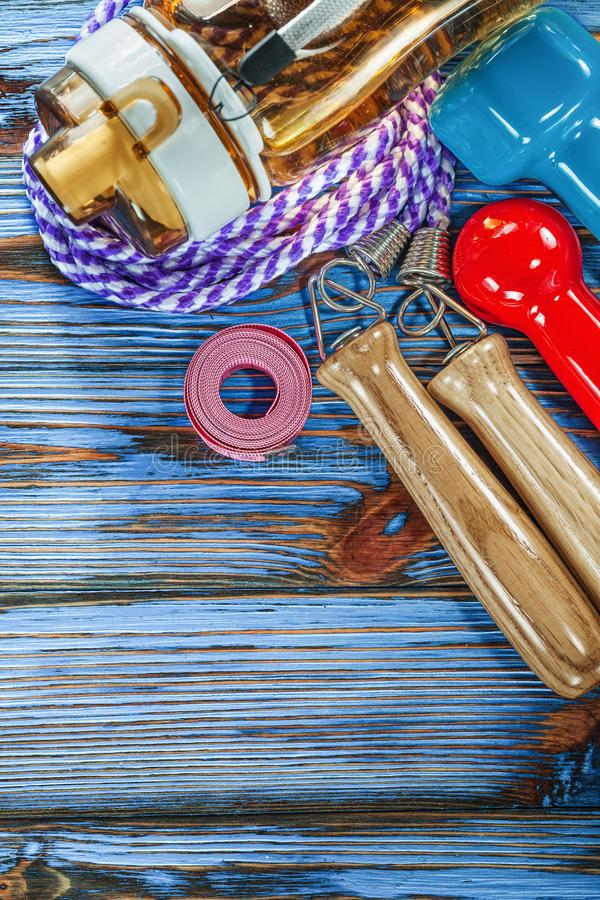 Measuring tape jump rope dumbbells water shaker on wooden board royalty free stock image
