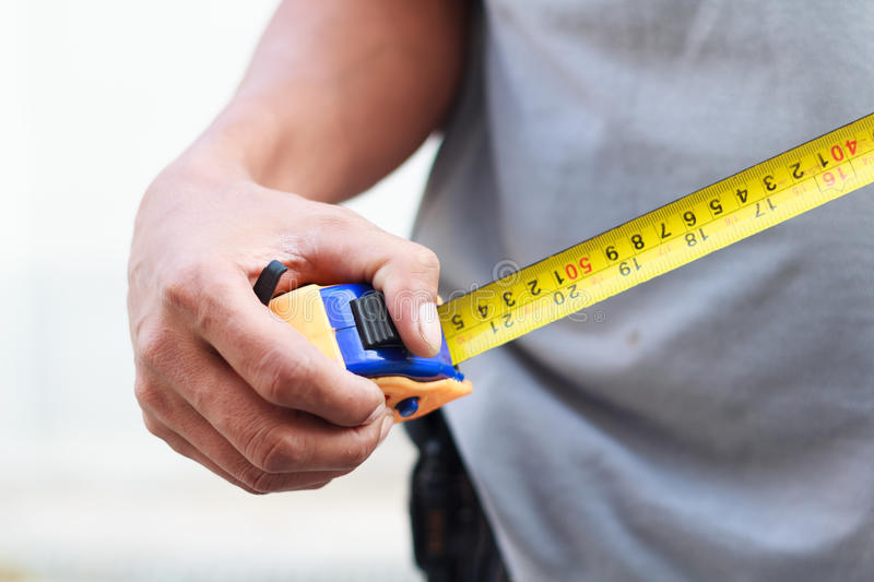 Measuring tape measure in hands. Photo of measuring tape measure in hands stock images