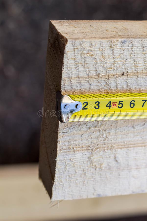 Measuring tape measure on the long board. Yellow Measuring tape measure on the board wood construction building meter metric accuracy background bricolage stock photography
