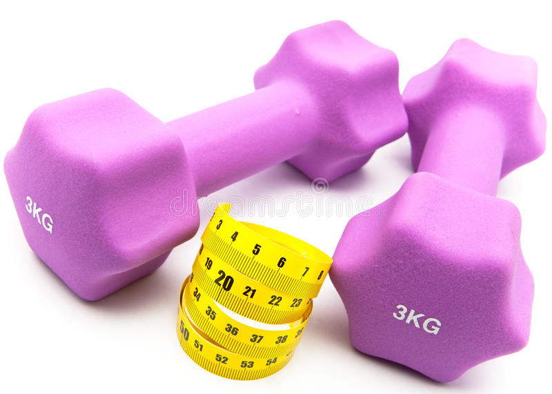 Sports equipment for occupation by fitness.measuring tape and and Pink dumbbells. Measuring tape and and Pink dumbbells stock images