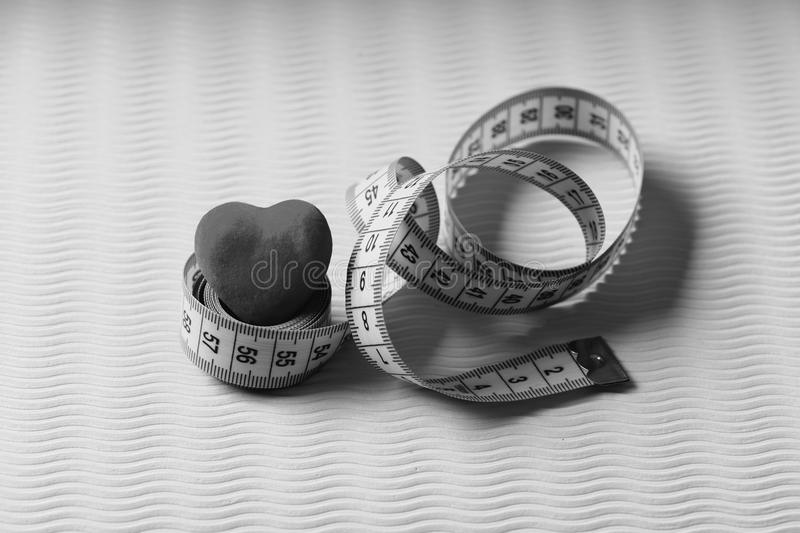 Measuring tape roll in cyan color and soft red heart on green texture background. Shaping and fitness. Sports and. Healthy lifestyle concept. Heart decoration royalty free stock photo