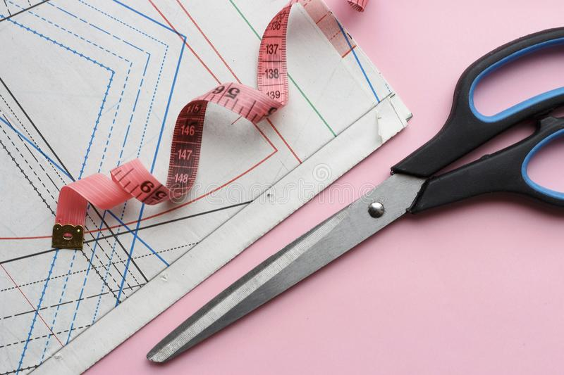 Measuring tape, scissors and sewing pattern for sewing on a pink background close-up, top view royalty free stock photo