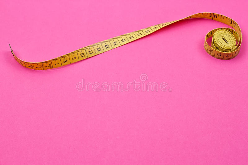 Measuring tape of the tailor. On the pink background royalty free stock images