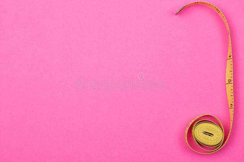 Measuring tape of the tailor. On the pink background stock images