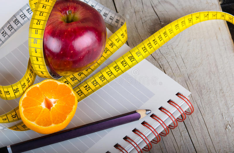 Measuring tape wrapped around a apple weight loss stock photography