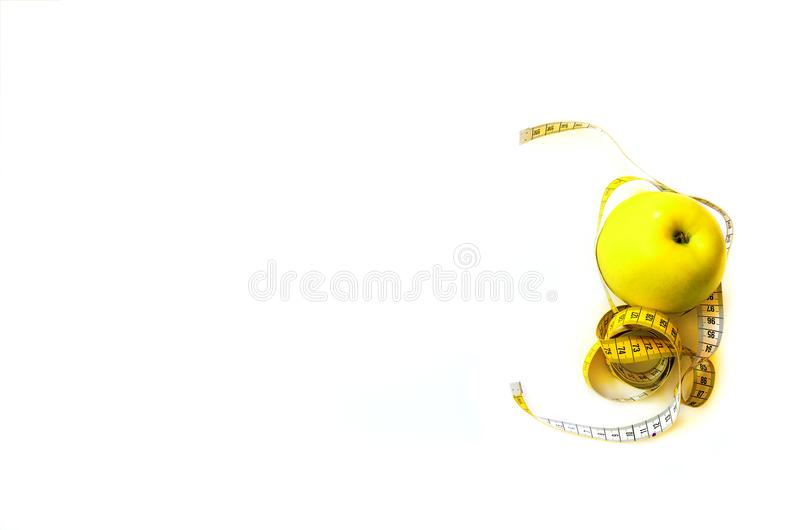 Measuring tape wrapped around fresh tasty yellow apple isolated on white background. Diet, weight loss, fitness, sport stock photos