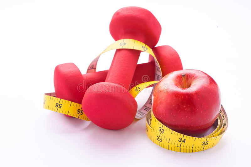 Measuring tape wrapped around a green apple and dumbells as a symbol of diet. royalty free stock image