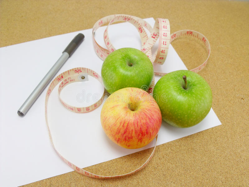 Measuring tape wrapped around a green apple stock image