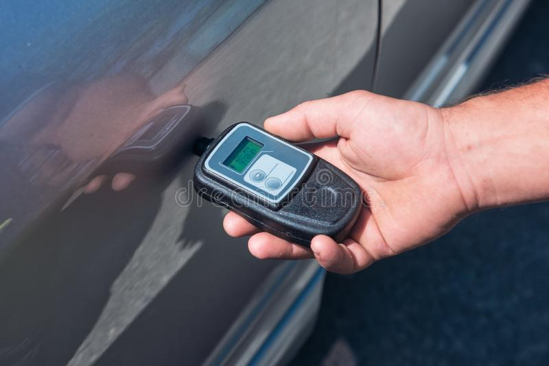 Measuring thickness of the car paint coating with paint thickness gauge stock photos